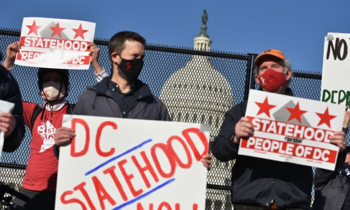 Activists hold signs as they take part in a rally in support of DC statehood near the US Capitol in Washington D.C., on March 22, 2021. (Mandel Ngan/AFP via Getty Images)