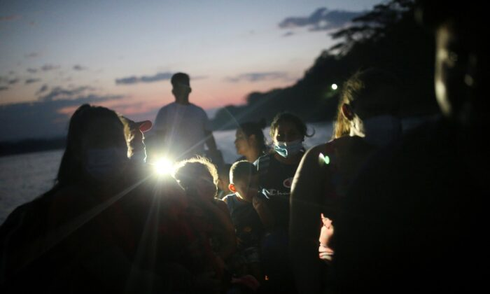 Honduran migrant families trying to reach the United States cross the Usumacinta river on a boat, at La Tecnica in Lacandon jungle, Guatemala, on March 6, 2021. (Edgard Garrido/Reuters)