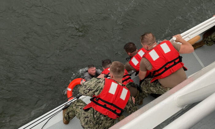 The crew of the Coast Guard Cutter Glenn Harris pulls a person from the water after a 175-foot commercial lift boat capsized 8 miles south of Grand Isle, Louisiana, on April 13, 2021. (USCG/Coast Guard Cutter Glenn Harris)