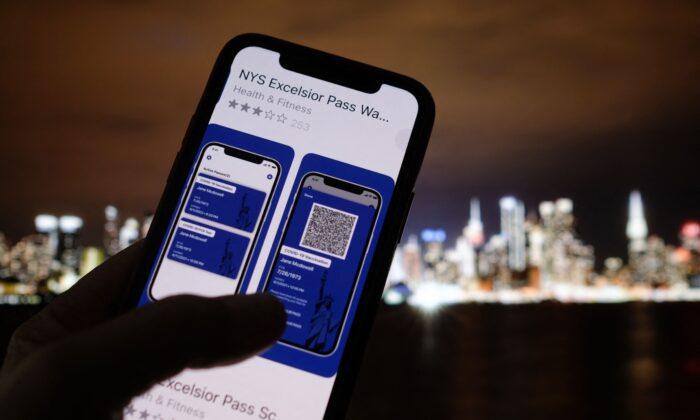 This illustration photo taken in Los Angeles on April 6, 2021 shows a person looking at the app for the New York State Excelsior Pass, which provides digital proof of a COVID-19 vaccination, in front of a screen showing the New York skyline. (Chris Delmas/AFP via Getty Images)