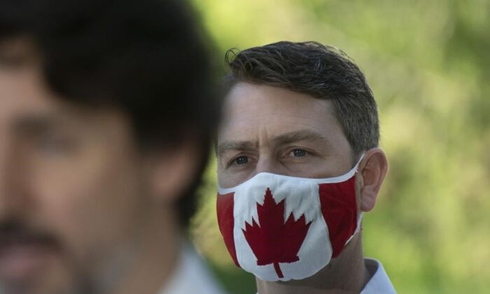 Liberal Member of Parliament William Amos wears a Canadian flag mask as Prime Minister Justin Trudeau speaks during a news conference in Chelsea , Que., on June 19, 2020. (Adrian Wyld / The Canadian Press)