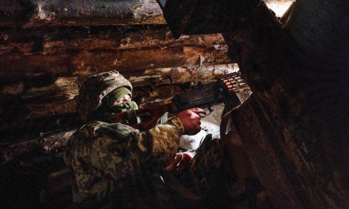 A Ukrainian serviceman keeps ready a machine gun in his shelter near the front-line town of Krasnohorivka, eastern Ukraine, on March 5, 2021. (Evgeniy Maloletka/AP Photo)
