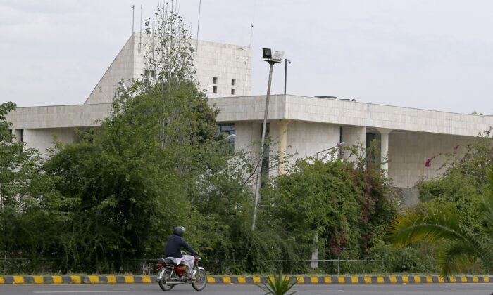 A motorcyclist rides past the French Embassy, in Islamabad, Pakistan, on April 15, 2021. (Anjum Naveed/AP Photo)