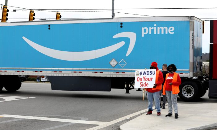 People hold a banner at the Amazon facility as members of a congressional delegation arrive to show their support for workers who will vote on whether to unionize, in Bessemer, Ala., on March 5, 2021. (Dustin Chambers/Reuters)