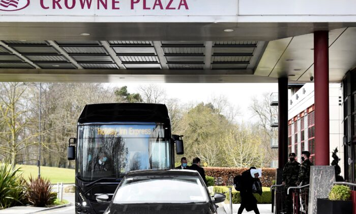 A passenger covers her face after getting off a designated quarantine bus at Crowne Plaza Dublin Airport Hotel, as Ireland introduces hotel quarantine programme for 'high-risk' countries' travellers, in Dublin, Ireland, on March 26, 2021. (Clodagh Kilcoyne/Reuters)