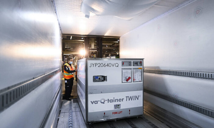 A FedEx worker loads the 255,600 doses of the Moderna COVID‑19 vaccine which came from Europe into a freezer trailer to be transported during the COVID-19 pandemic at Pearson International Airport in Toronto on March 24, 2021. (Nathan Denette/The Canadian Press)