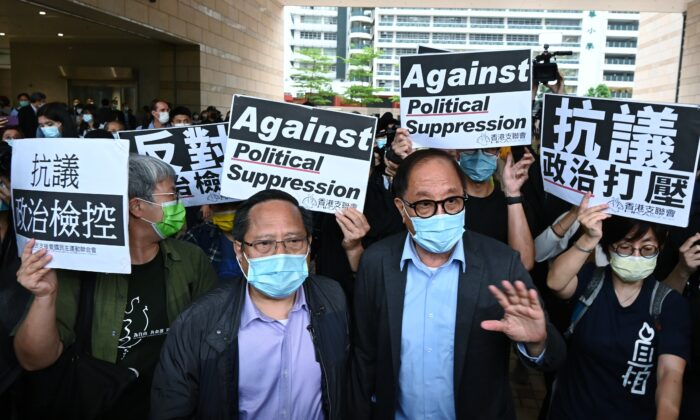 (L-R) Alberto Ho and Yeung Sum leave the West Kowloon court builiding after being given suspended sentences in Hong Kong on April 16, 2021. (Song Pi-lung/The Epoch Times)