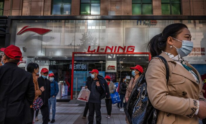 Tourists and shoppers walk by a Li-Ning store, a Chinese sportswear brand, at a shopping district in Beijing, China, on April 16, 2021. (Kevin Frayer/Getty Images)