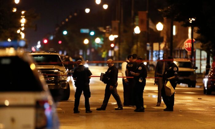 Police officers investigate the scene of a shooting in Chicago, Ill., on July 21, 2020. (Kamil Krzaczynski/AFP via Getty Images)
