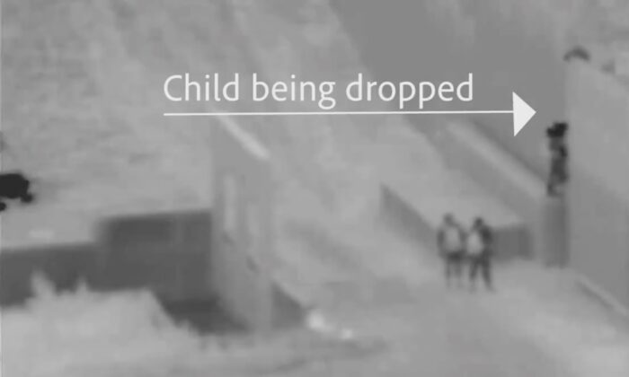 Video screenshot shows a human smuggler dropping a child over the U.S. border into San Diego, Calif., on April 11, 2021. (U.S. Customs and Border Protection)