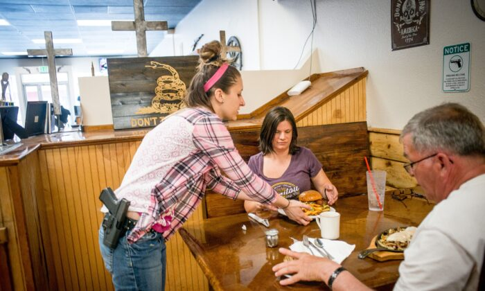 Waitress Jessie Spaulding serves customers at Shooters Grill in Rifle, Co. on April 24, 2018. (Emily Kask/AFP via Getty Images)