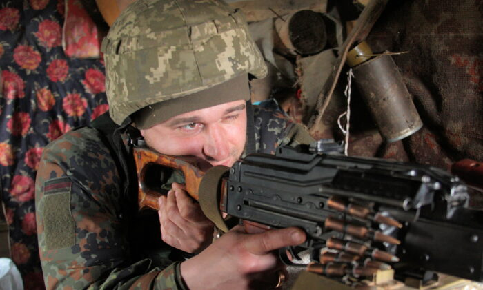 A service member of the Ukrainian armed forces points a weapon at fighting positions on the line of separation near the rebel-controlled city of Donetsk, Ukraine, on Apr. 16, 2021. (Serhiy Takhmazov/ Reuters)