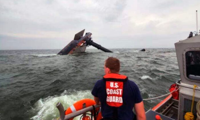 A Coast Guard Station Grand Isle 45-foot Response Boat-medium boat crew member searches for survivors near the capsized SeaCor Power. The Seacor Power, an oil industry vessel, flipped over in a microburst of dangerous wind and high seas, Tuesday, April 13, 2021. (U.S. Coast Guard via AP)