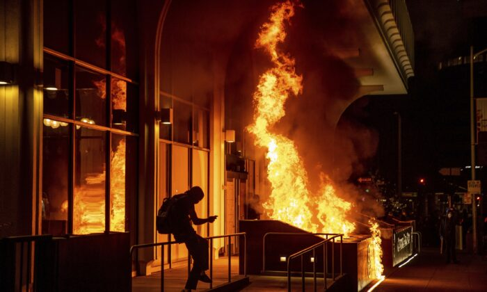 Rioters set fire to the California Bank and Trust building in Oakland, Calif., on April 16, 2021. (Ethan Swope/AP Photo)
