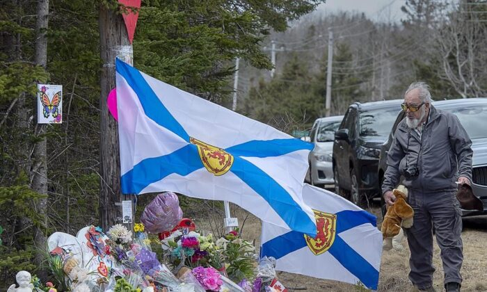A man pays his respects at a roadside memorial on April 23, 2020, in Portapique, N.S.  (The Canadian Press/Andrew Vaughan)