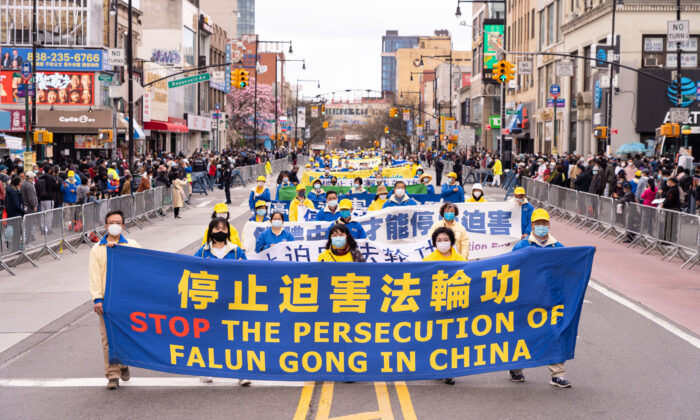 Falun Gong practitioners take part in a parade in Flushing, New York, on April 18, 2021, to commemorate the 22nd anniversary of the April 25th peaceful appeal of 10,000 Falun Gong practitioners in Beijing. (Larry Dye/The Epoch Times)