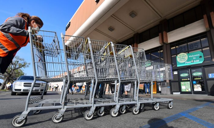 """A Food 4 Less employee pushes carts past supermarket workers gathered to protest in front of the supermarket in Long Beach, Calif. on Feb. 3, 2021, after a decision by owner Kroger to close two supermarkets rather than pay workers an additional $4 in """"hazard pay"""" for their continued work during the COVID-19 pandemic. (Frederic J. Brown/AFP via Getty Images)"""