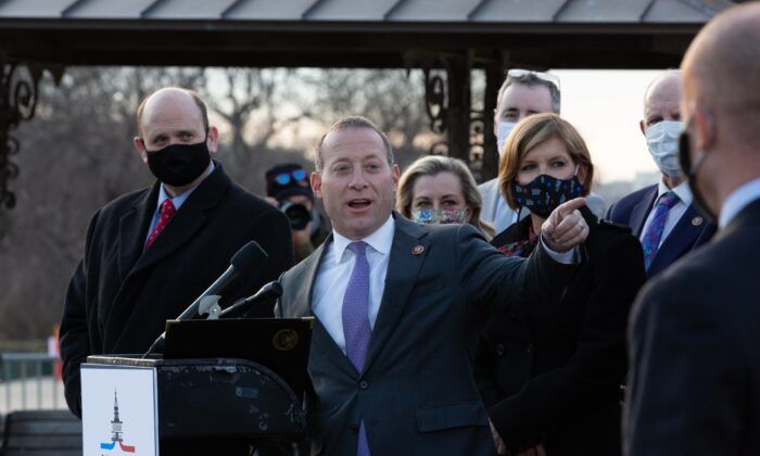 Rep. Josh Gottheimer (D-NJ) speaks at the podium standing with members of the Problem Solvers Caucus to praise the forthcoming passage of the bipartisan emergency COVID-19 relief bill in a press conference outside the US Capitol in Washington on December 21, 2020. (Cheriss May/Getty Images)