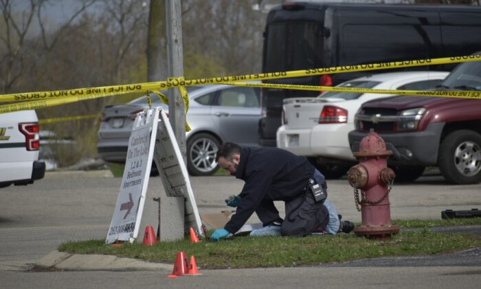 An investigator looks for evidence outside the Somers House Tavern, after a fatal shooting, in Somers, Wis., just outside of Kenosha, on April 18, 2021. (Deneen Smith/The Kenosha News via AP)