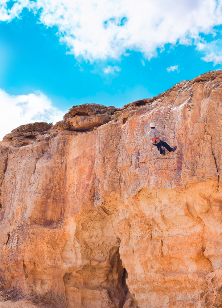 Climber,Rappelling,Down,A,Cliff,In,Mitzpe,Ramon,Crater,,Israel.