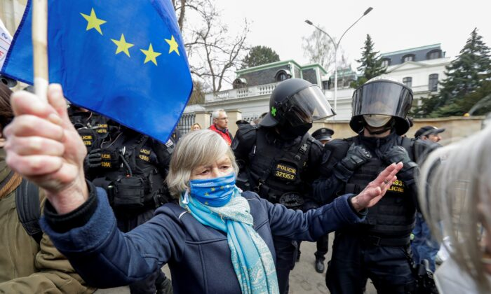A woman holds an EU flag next to police officers during a protest over the Russian intelligence services alleged involvement in an ammunition depot explosion in Vrbetice area in 2014, outside the Russian Embassy in Prague, Czech Republic, on April 18, 2021. (David W Cerny/Reuters)