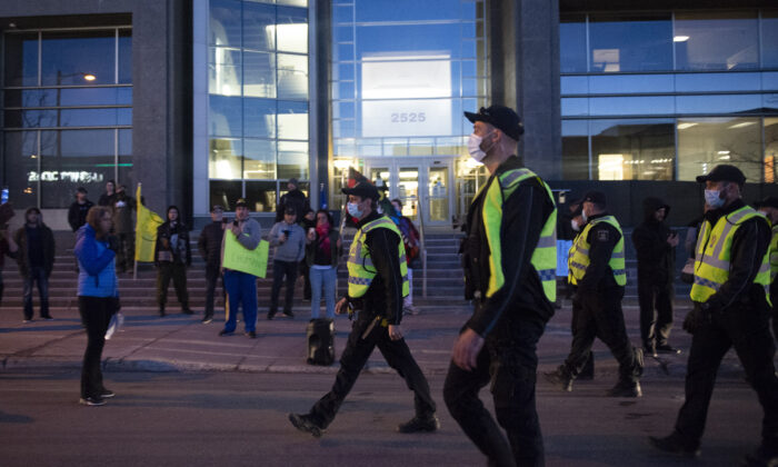 Police officers walk toward anti-curfew demonstrators in front of Quebec Deputy premier and Public Security Minister Genevieve Guilbault's office in Quebec City on April 13, 2021. (Jacques Boissinot/The Canadian Press)