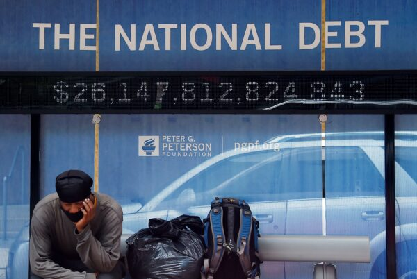 A man waits at a bus stop that displays the official national debt of the United States in Washington on June 19, 2020. The non-profit Truth-in-Accounting says the actual national debt is more than four times the official figure. (Olivier Douliery/AFP via Getty Images)