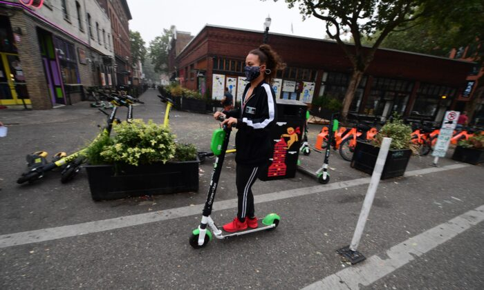 A woman wears a mask as she rides a scooter in downtown Portland, Ore., on Sept. 14, 2020. (Robyn Beck/AFP via Getty Images)