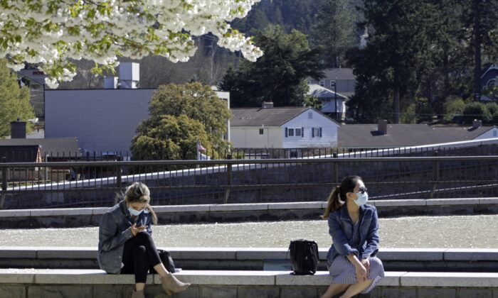 Residents wearing masks sit in downtown Lake Oswego, Ore., on April 11, 2021. (Gillian Flaccus/AP Photo)