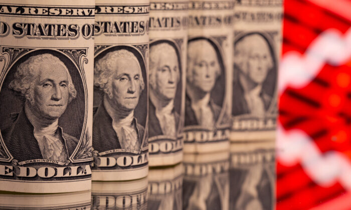 U.S. one dollar banknotes are seen in front of displayed stock graph in this illustration on Feb. 8, 2021. (Dado Ruvic/Reuters)