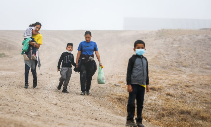 A group of illegal immigrants walk towards Border Patrol after crossing the U.S.-Mexico border in La Joya, Texas, on April 10, 2021. (Charlotte Cuthbertson/The Epoch Times)