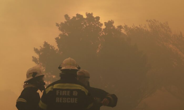 Firefighters keep an eye on a raging fire on the slopes of Table Mountain, in Cape Town  South Africa, Monday, April 19, 2021. Residents in the Vredehoek suburb have been evacuated as a precautionary measure as high winds fanned the fire for a second day. (AP Photo/Nardus Engelbrecht)