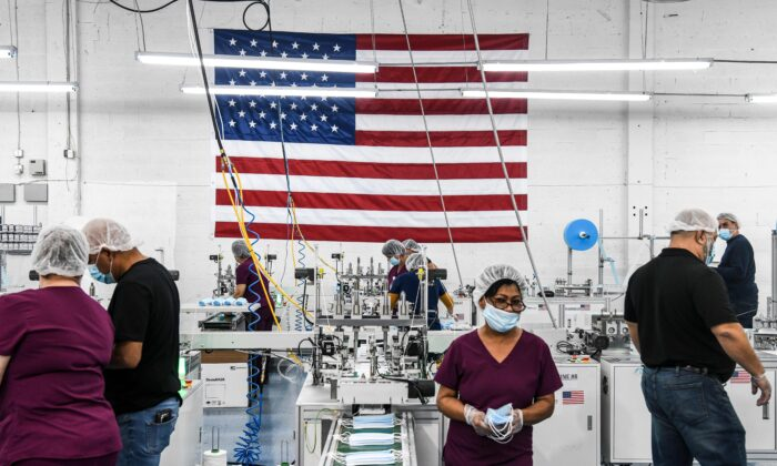 Employees work as they make respiratory masks in a family-owned medical equipment factory in north Miami, Fla., on Feb. 15, 2021. (Chandan Khanna/AFP via Getty Images)