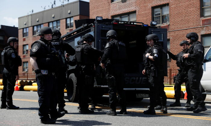 Law enforcement officers stand near the place where the shooter barricaded himself, after a shooting at a Stop and Shop grocery store, in Hempstead, N.Y., on April 20, 2021.  (Shannon Stapleton/Reuters)