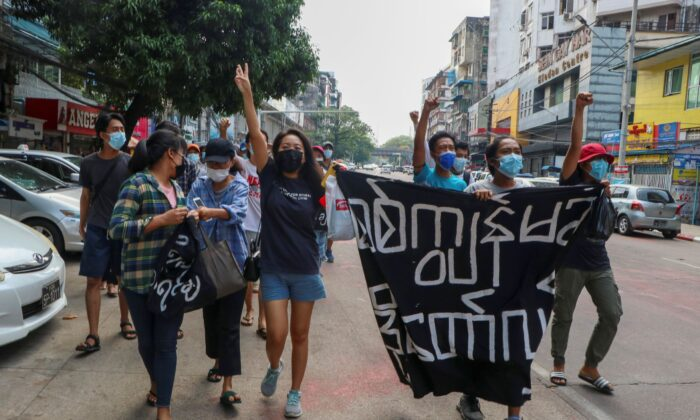 Anti-coup protesters shout slogans with a banner reading ''Carry on revolution! We do not accept as the military slave,'' in Kamayut township of Yangon, Burma, on April 19, 2021. (AP Photo)