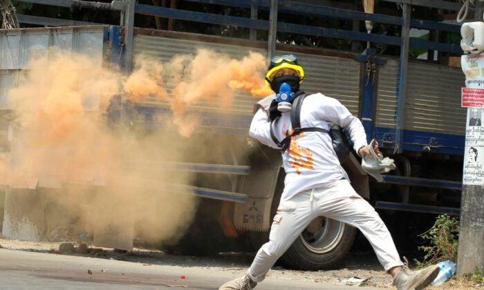 An anti-coup protester throws a smoke bomb against police during a crackdown in Thaketa township in Yangon, Burma, on March 27, 2021. (AP Photo)