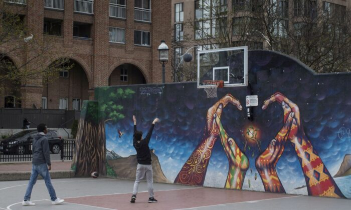Two youths play basketball in an otherwise quiet court in Toronto on April 17, 2021. (The Canadian Press/Chris Young)