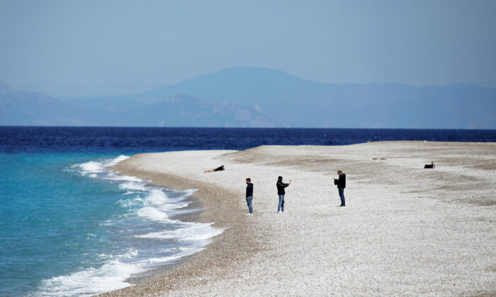 People stand on Elli Beach, amid the coronavirus disease (COVID-19) pandemic, on the island of Rhodes, Greece on April 12, 2021. (Louiza Vradi/Reuters)