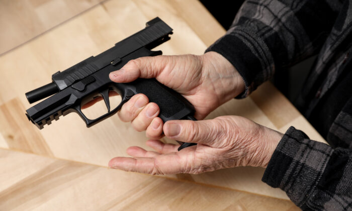 A magazine is loaded into a Sig Sauer P320 compact semi-auto pistol at a gun shop in Richmond, Va., on Jan. 13, 2020. (Samira Bouaou/The Epoch Times)