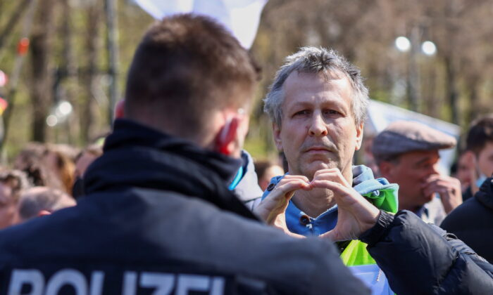 A man gestures to the police as he takes part in a protest against the government measures to curb the spread of the coronavirus disease (COVID-19), as the lower house of parliament Bundestag discusses additions for the Infection Protection Act, in Berlin, Germany, on April 21, 2021. (Christian Mang/Reuters)