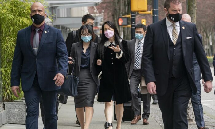 Meng Wanzhou, chief financial officer of Huawei, walks down the street with an acquaintance after leaving B.C. Supreme Court during a lunch break at her extradition hearing, in Vancouver, B.C., on April 1, 2021. (THE CANADIAN PRESS/Rich Lam)