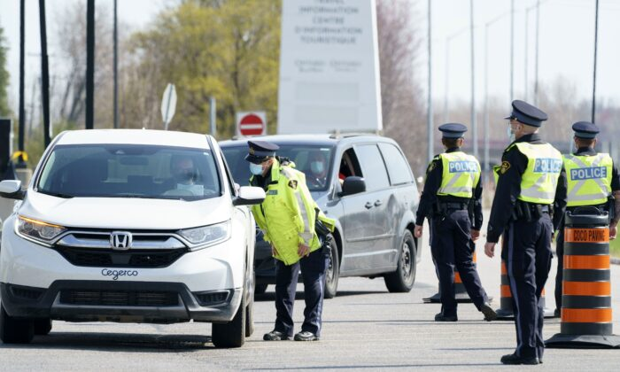 Motorists are screened at a police check point to limit non-essential travel from Quebec at the entrance of the province of Ontario on Highway 401 near Bainsville, Ont. on April 19, 2021. (The Canadian Press/Paul Chiasson)