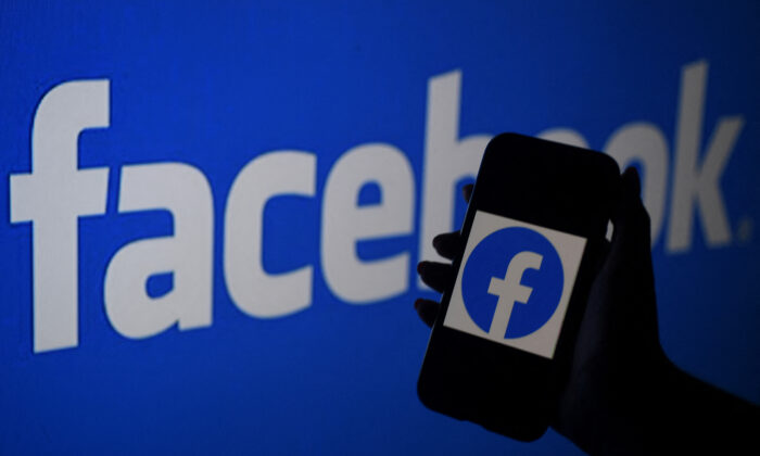 In this photo illustration, a smart phone screen displays the logo of Facebook on a Facebook website background, in Arlington, Va., on April 7, 2021. (Olivier Douliery/AFP via Getty Images)