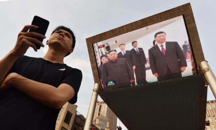 A man waits for a taxi as news footage of Chinese leader Xi Jinping (R) being greeted in Pyongyang by North Korean leader Kim Jong Un is shown on a large screen behind him outside a shopping mall in Beijing, China, on June 20, 2019. (Greg Baker/AFP via Getty Images)