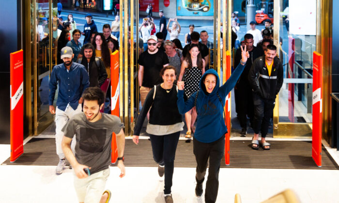 Customers run through the doors of the David Jones Elizabeth Street store for the 6am opening during the Boxing Day sales on Dec. 26, 2019, in Sydney, Australia. (Jenny Evans/Getty Images)