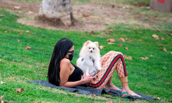 A woman wearing a facemask sits with her dog at Pan Pacific Park amid the coronavirus pandemic, November 6, 2020, in Los Angeles, California. (Photo by VALERIE MACON / AFP) (Photo by VALERIE MACON/AFP via Getty Images)