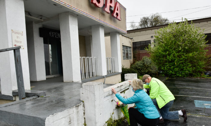 John and Barbara Hayes of Sandy Springs, Ga., bring flowers and offer prayers at the steps of Gold Spa, one of the three Asian massage parlors that were the sites of deadly attacks on March 16, 2021 in Northeast Atlanta, Ga., on March 17, 2021. (Virginie Kippelen/AFP via Getty Images)