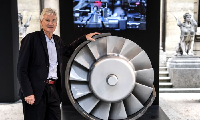 British industrial design engineer and founder of the Dyson company, James Dyson, poses next to the model of an engine during a photo session at a hotel in Paris on Oct. 11, 2018. (Christophe Archambault/AFP via Getty Images)