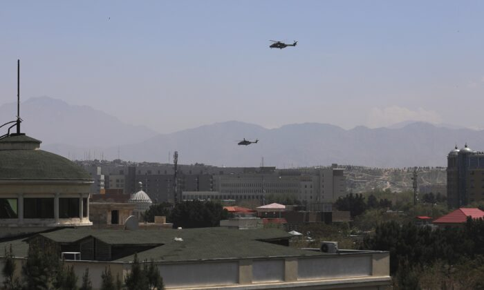 U.S. Black Hawk military helicopters fly over the city of Kabul, Afghanistan, on April 19, 2021. (Rahmat Gul/AP Photo)