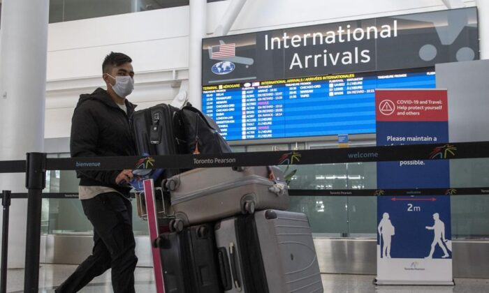 A passenger from Air India flight 187 from New Delhi arrives at Pearson Airport in Toronto on April 21, 2021. (The Canadian Press/Frank Gunn)